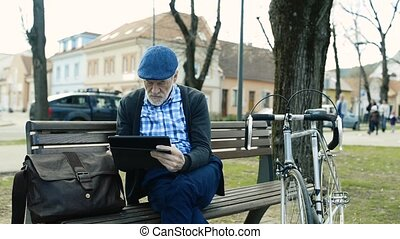 Senior man in town sitting on bench, working on tablet -...