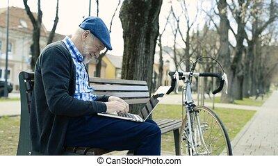 Senior man in town sitting on bench, working on laptop -...