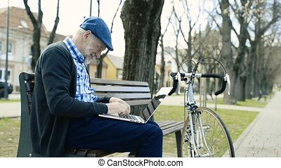 Senior man in town sitting on bench, working on laptop