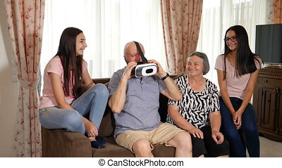 Senior man in virtual reality headset or 3d glasses having fun with family