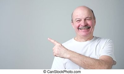 Senior man in white t-shirt pointing with index finger to...