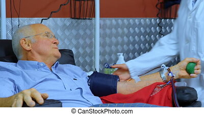Senior man interacting with physician while donating blood 4k