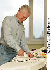 Senior man ironing