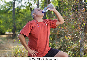 senior man is drinking water after workout in park