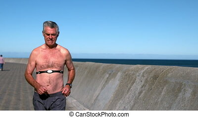 Senior man jogging shirtless on sunny day in slow motion