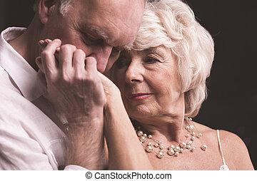 Senior man kissing female hand