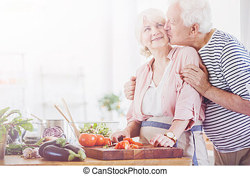 Senior man kissing woman in the kitchen