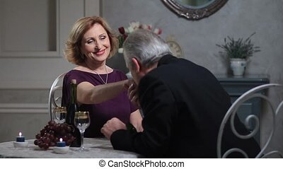 Senior man kissing woman's hand