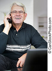 Senior man laughing whilst on the telephone