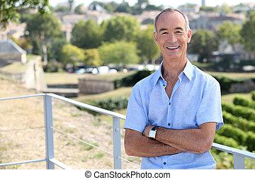 Senior man leaning against railing