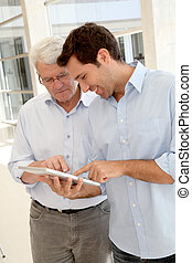 Senior man learning how to use electronic tablet