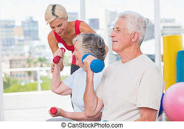 Senior man lifting dumbbells while trainer assisting woman at gy