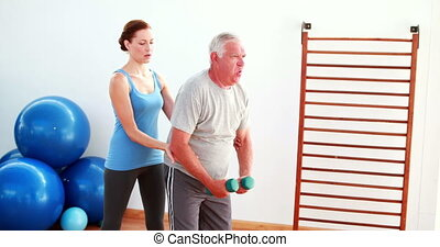 Senior man lifting hand weights with the help of his trainer...