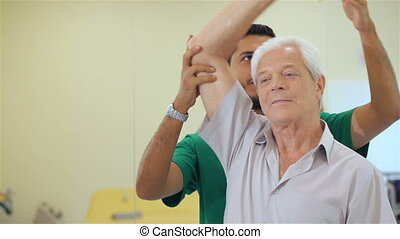 Senior man lifts up the dumbbell at the hospital