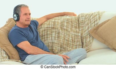 Senior man listening to music with headphones