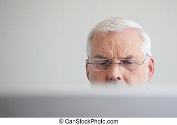Senior man looking at a laptop