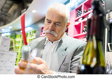 senior man looking at bottle of wine