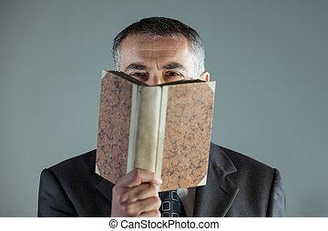 Senior man looking at camera behind an old book