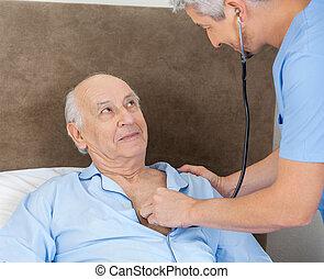 Senior Man Looking At Caretaker Examining Him With Stethoscope