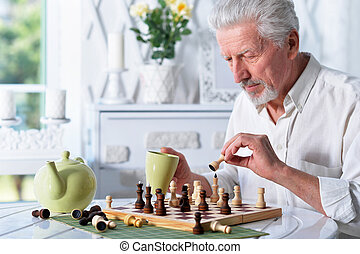 Senior man looking at chess board while drinking tea at home