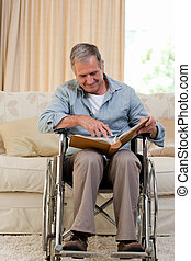 Senior man looking at his photo album