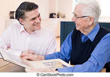 Senior Man Looking At Photo Album With Adult Son