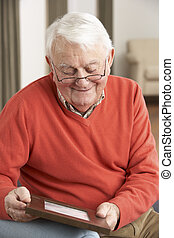 Senior Man Looking At Photograph In Frame