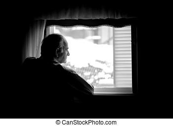 Senior man looking at the window