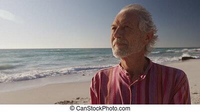 Senior man looking away at the beach - Front view close up ...