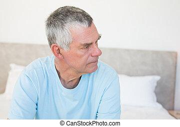 Senior man looking away on bed