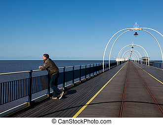 Senior man looking out over beach at Southport