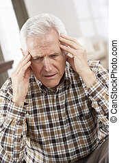 Senior Man Looking Stressed In Chair At Home