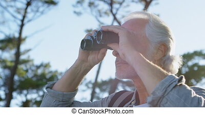 Senior man looking through binoculars at countryside 4k -...