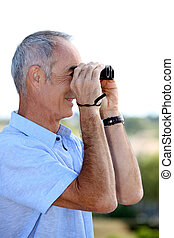 senior man looking through binoculars