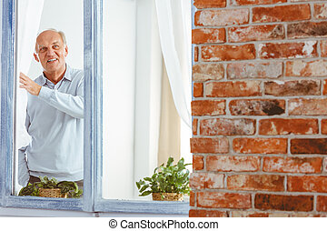 Senior man looking through window - Happy smiling elegant...