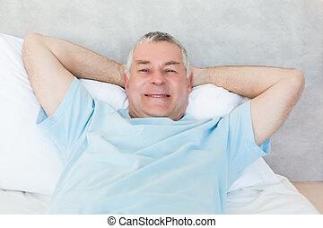 Senior man lying in bed