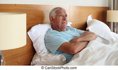 Senior man lying in bed thinking at home in the bedroom