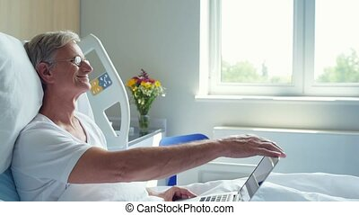 Senior man lying in the hospital bed with laptop