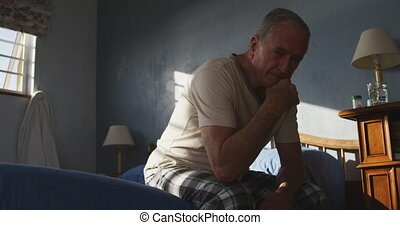 Senior man lying on bed at home