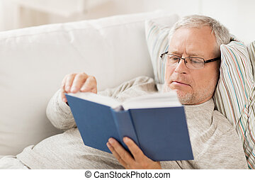 senior man lying on sofa and reading book at home