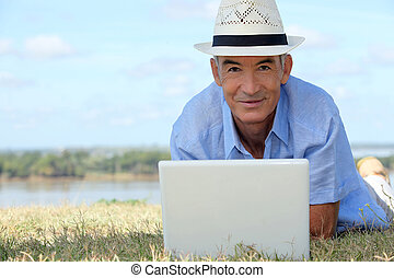 Senior man lying on the grass with a computer