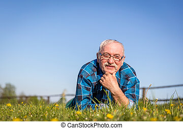 Senior man lying on the summer field in green grass.