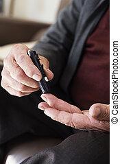 senior man measuring his blood glucose level - closeup of a ...