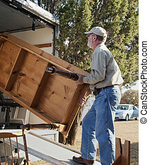 Senior Man Moving a Table - Senior man moving a table into...
