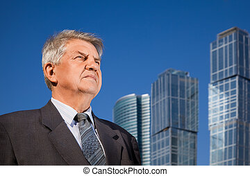 senior man near skyscrapers construction
