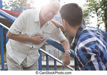 Senior man needing first aid - Senior man with heart attack...