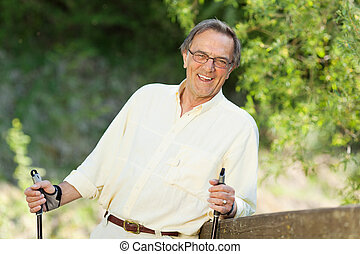 Senior man nordic walking in the park - Cheerful senior man...