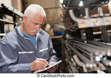 Senior man noting stock of metal rods