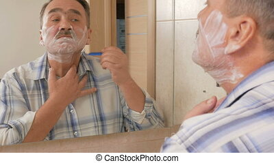 Senior man of shaving in the bathroom. It uses shaving foam and disposable razor. The concept of self-care
