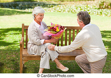 Senior man offering flowers to his